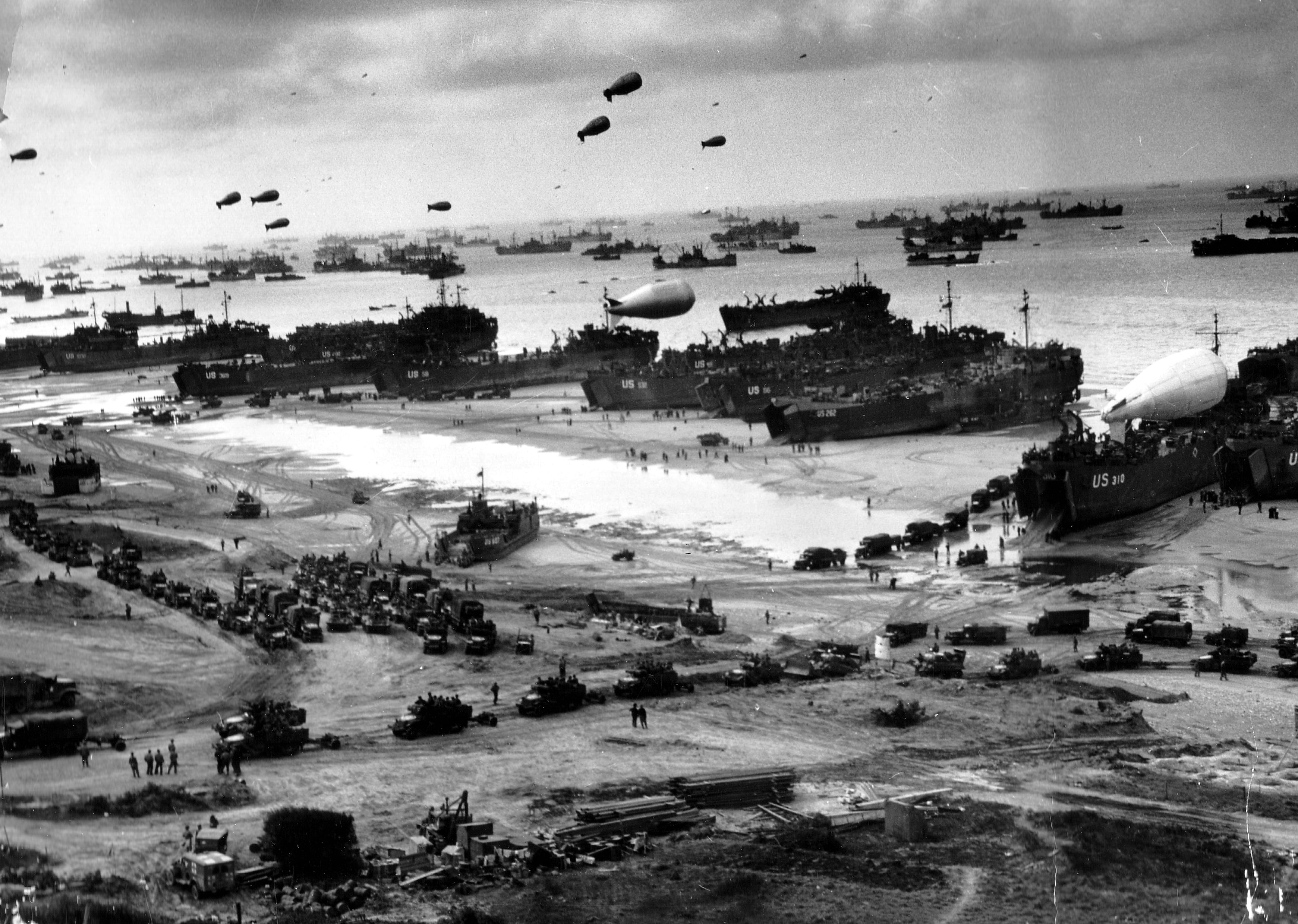 Landing craft and ships unload troops and supplies at Omaha